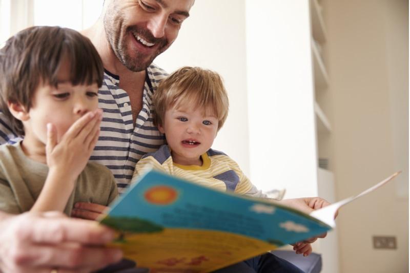 Vater und Söhne lesen gemeinsam die Geschichte zu Hause