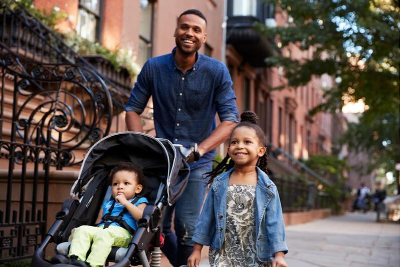 Vater und zwei Töchter gehen die Straße entlang