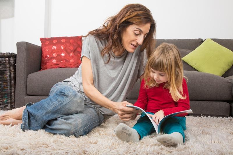 blondes Kind drei Jahre alt, das ein Buch liest