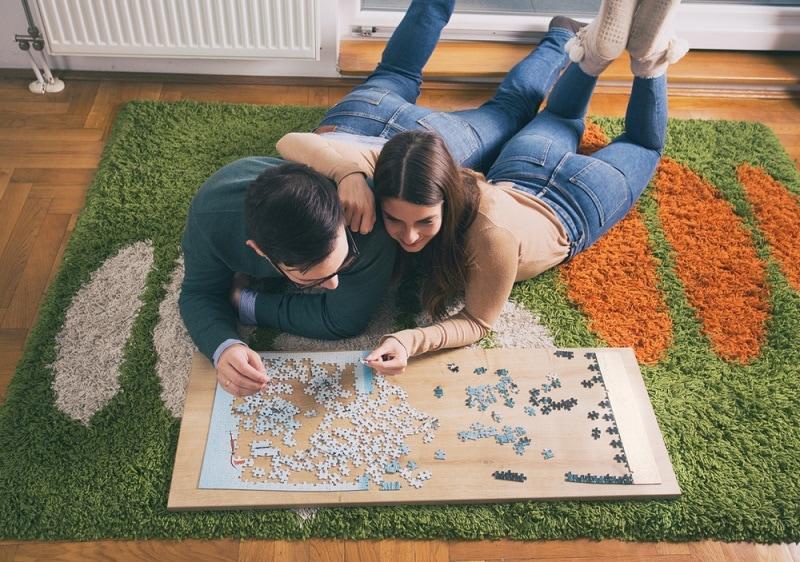 ein Paar macht ein Puzzle auf dem Boden des Wohnzimmers