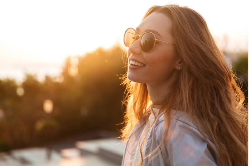 glückliche brünette Frau mit Sonnenbrille