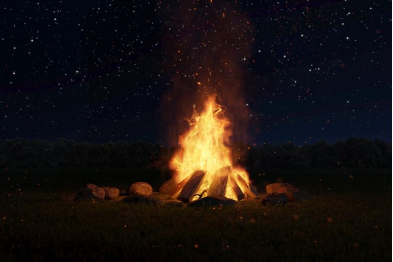 großes Lagerfeuer mit Funken und Partikeln vor Wald