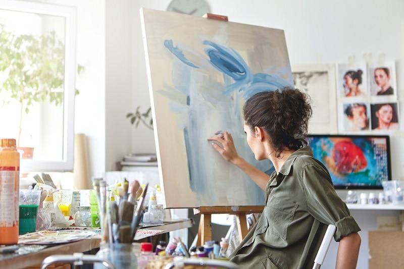 Junge Frau malt zu Hause mit ihren Fingern