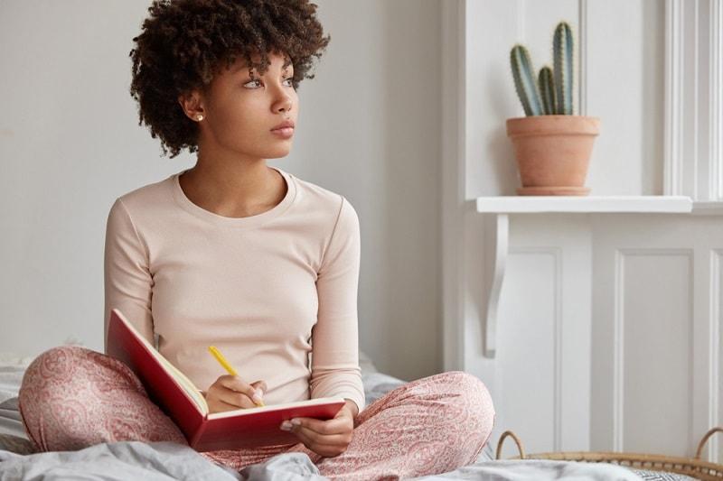 Junge Frau schreibt in ihrem Schlafzimmer in ein Tagebuch