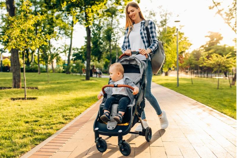 junge Mutter geht mit einem kleinen Kleinkind im Kinderwagen spazieren