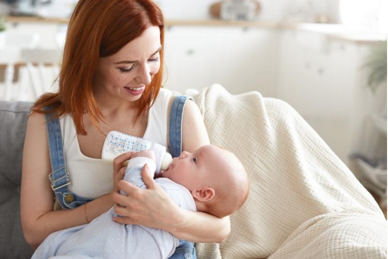 junge Mutter mit dem Füttern ihres Babys aus der Milchflasche