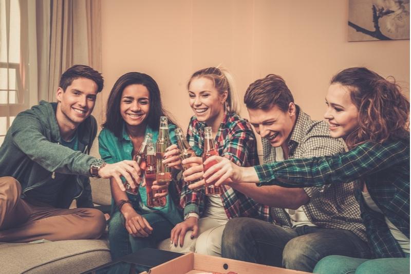 junge multiethnische Freunde mit Pizza und Getränkeflaschen, die zu Hause feiern