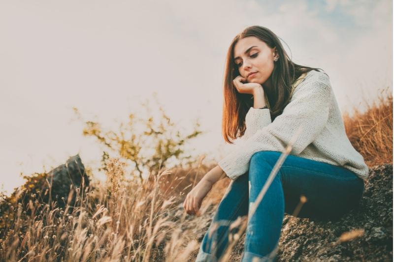 junges Mädchen sitzt allein auf einem Stein
