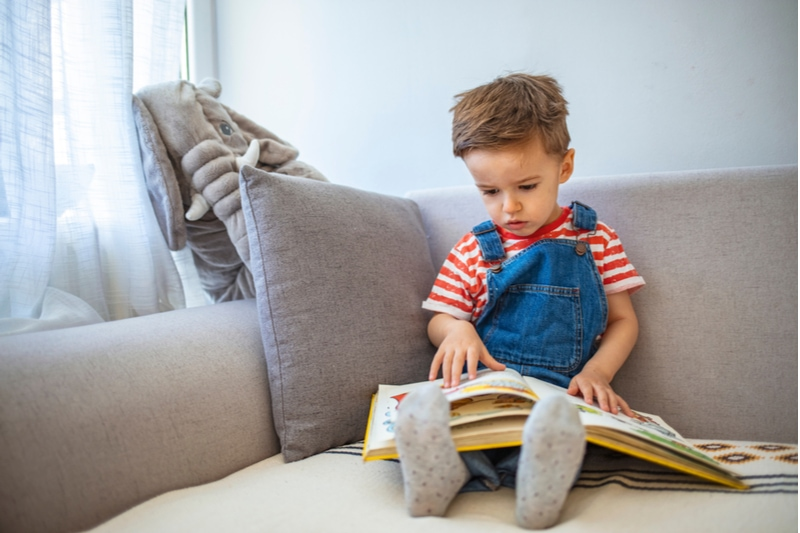 kleiner Junge, der zu Hause ein Buch liest