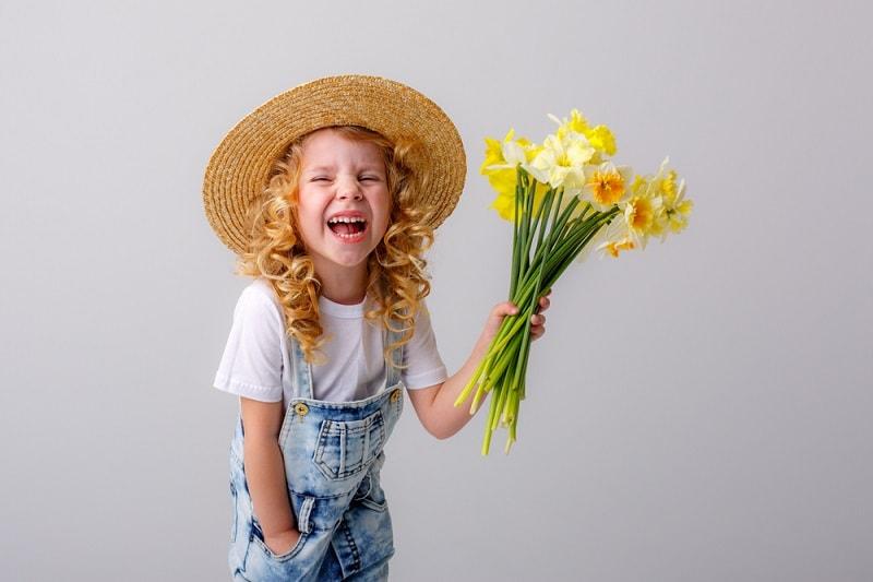 kleines Mädchen mit lockigem blondem Haar lächelt und hält Blumen