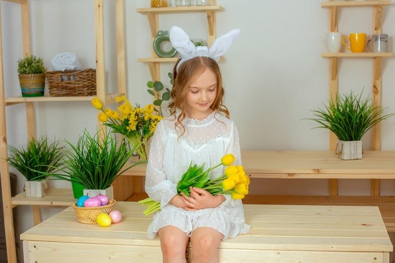 kleines Mädchen mit blonden Haaren hält gelbe Tulpen in der Küche