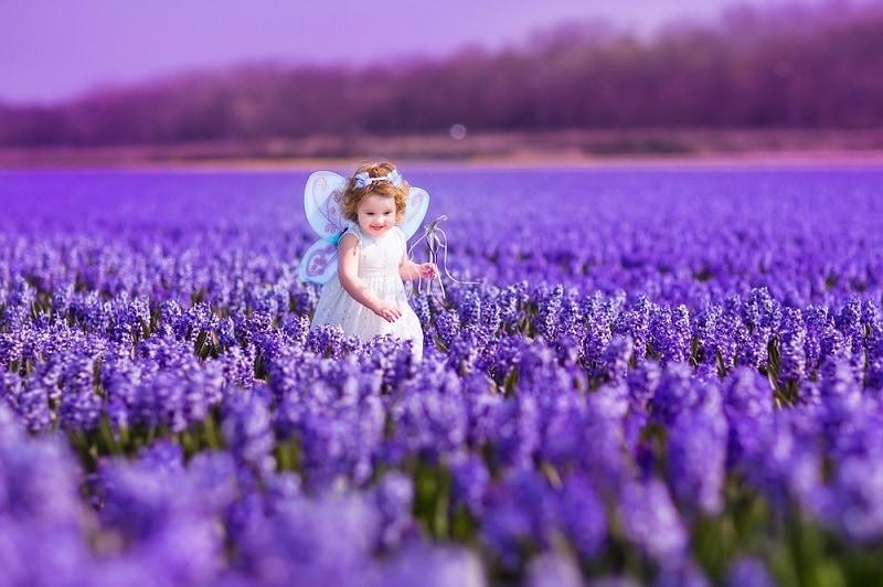 kleines Mädchen trägt ein schönes Kleid und geht in einem lila Blumenfeld