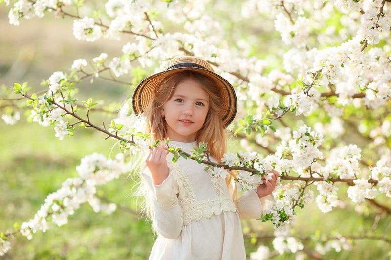 kleines Mädchen mit Hut, das neben einem blühenden Baum steht