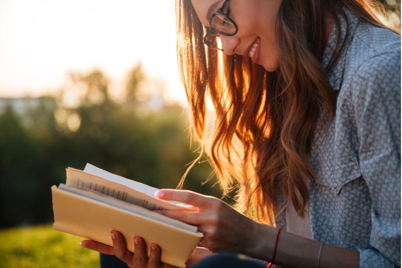 lächelnde Frau, die ein Buch im Park liest