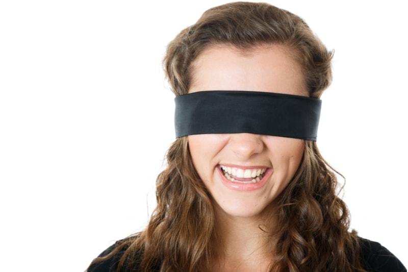 lächelnde junge Frau mit schwarzer Augenbinde
