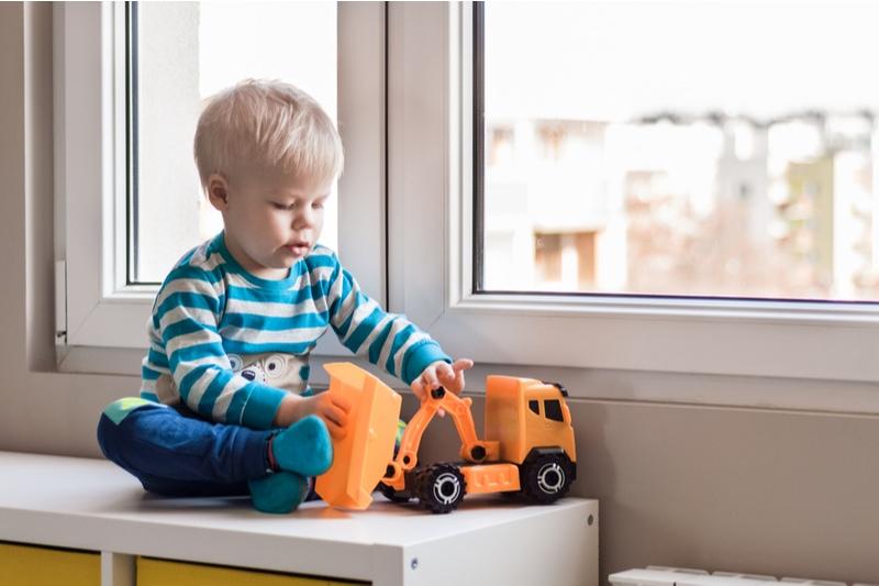 zweijähriger Junge sitzt am Fenster und spielt mit Spielzeuglaster