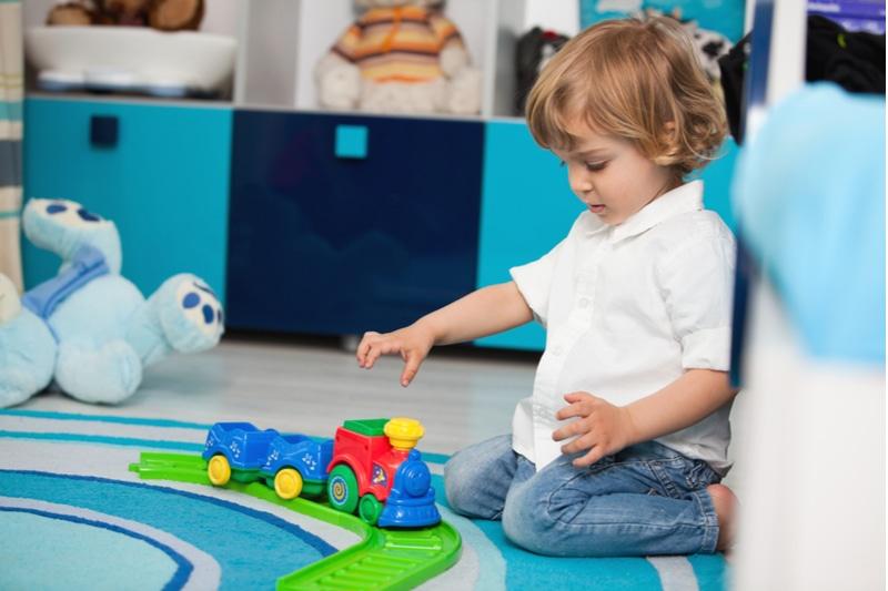 zweijähriges Kind spielt in seinem Zimmer mit einer Spielzeugeisenbahn