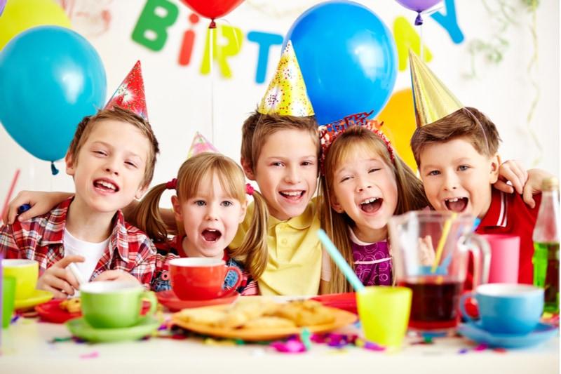 Gruppe entzückender Kinder, die Spaß auf der Geburtstagsfeier haben
