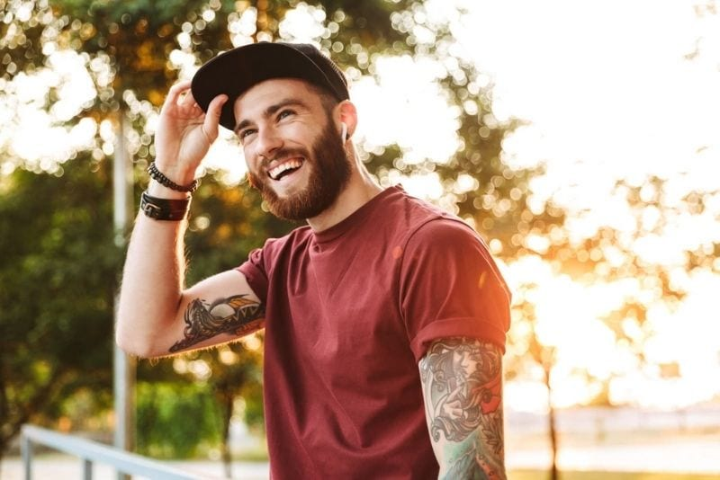 Hübscher junger Mann in Freizeitkleidung, der im Park spazieren geht