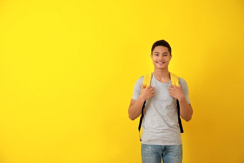 Jugendlicher mit Rucksack vor einem gelben Hintergrund