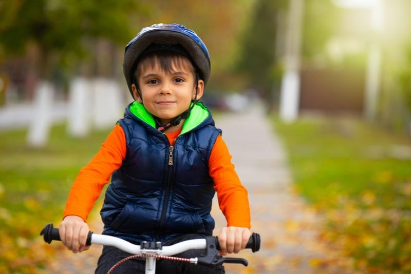 Junge, der einen Helm trägt und an einem Herbsttag Fahrrad fährt