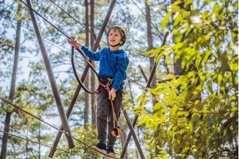 Junge, der in einem Kletterabenteuerpark genießt