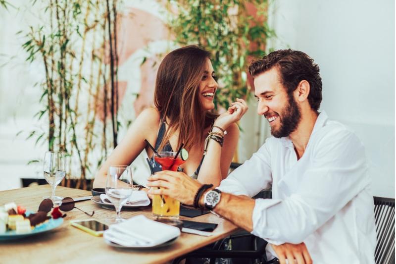 Junges Paar sitzt in der Außenbar und trinkt Cocktails