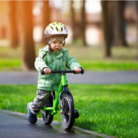 kleiner Junge mit Helm und Winterjacke fährt auf einem Laufrad