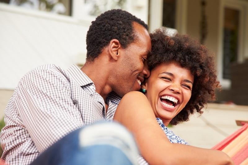 Paar, das sich umarmt und lächelt, während es in einer Hängematte liegt