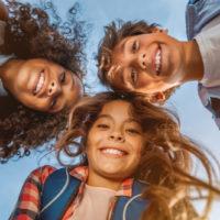 drei entzückende glückliche Kinder, die lächeln