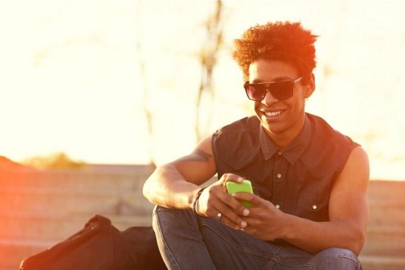Teenager, der Handy hält und lächelt