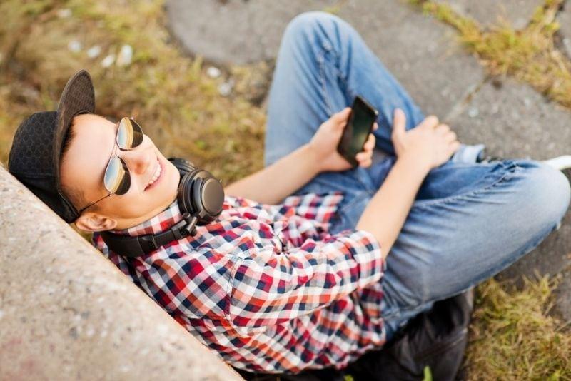 Teenager mit Kopfhörern und Smartphone draußen