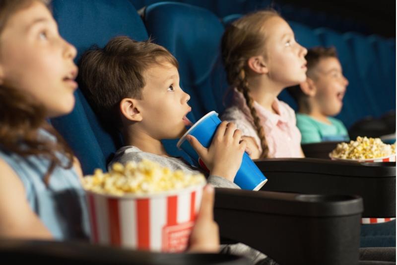 glückliche Kinder, die einen Film im Kino ansehen