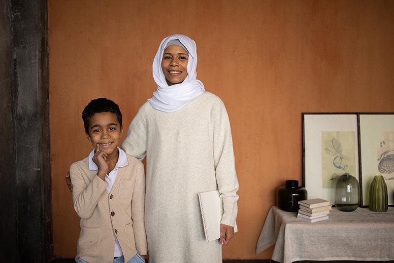 Arabische Mutter im Hijab mit glücklichem Sohn, der im Raum steht