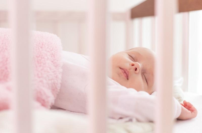 Das kleine Mädchen schläft in ihrem Bettchen