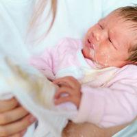 Mutter hält ihr neugeborenes Baby, das Milch spuckt