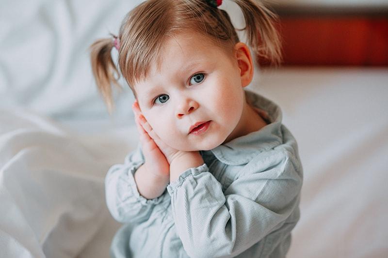 Babymädchen lehnt den Kopf auf die Handflächen und sitzt auf dem Bett