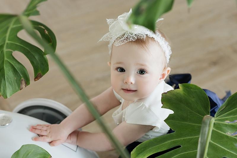 Babymädchen mit weißem Band auf dem Kopf, das neben Pflanzen im Haus steht