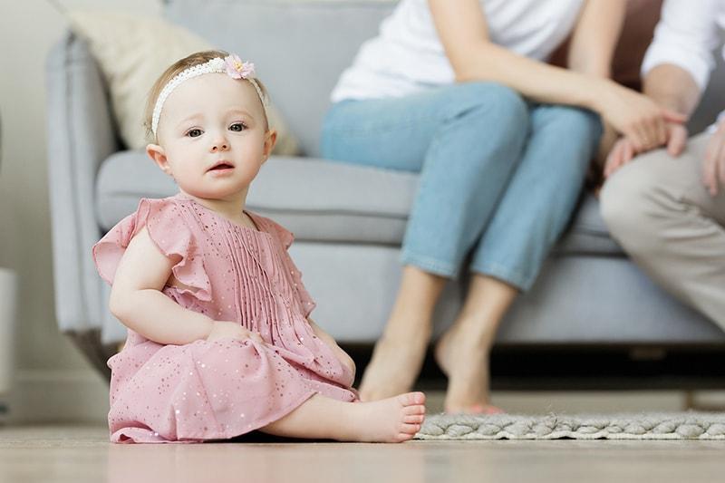 Baby Mädchen sitzt auf dem Boden vor den Eltern sitzen auf der Couch