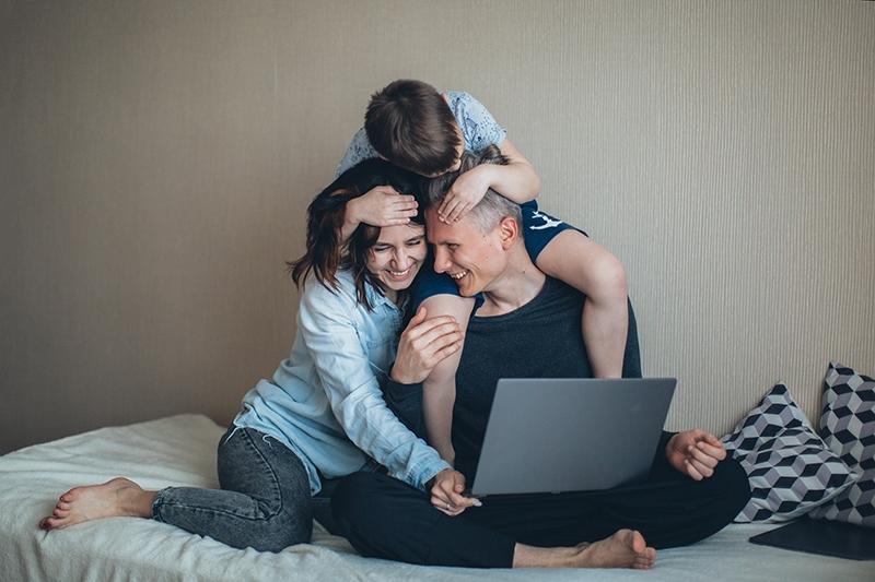 Eltern lachen mit seinem Sohn, während er auf dem Bett sitzt