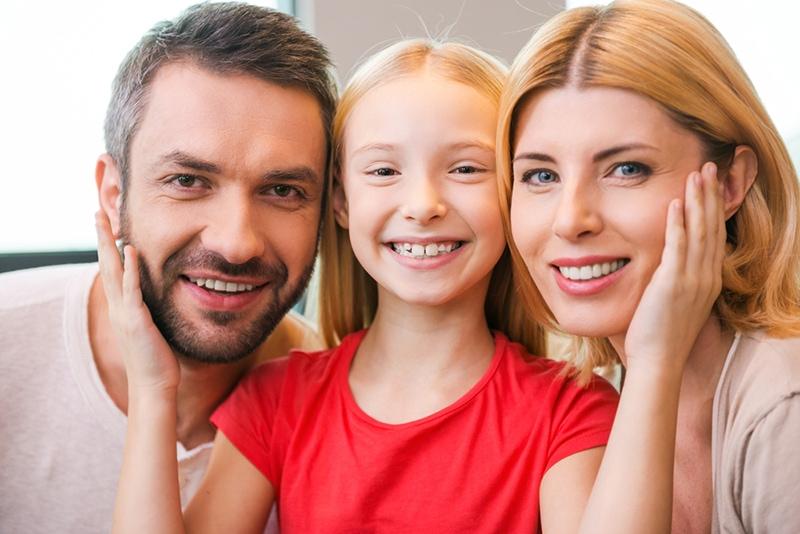 Eltern mit Tochter in der Mitte lächelnd