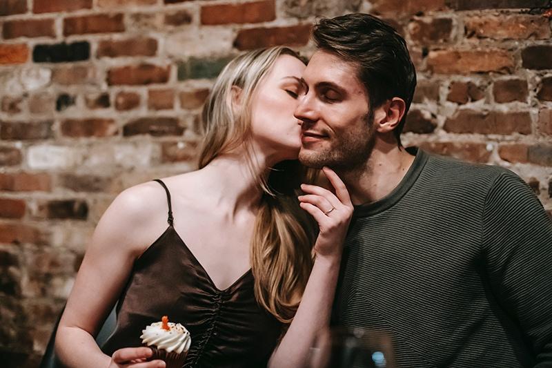Frau küsst Mann auf die Wange und hält einen Cupcake
