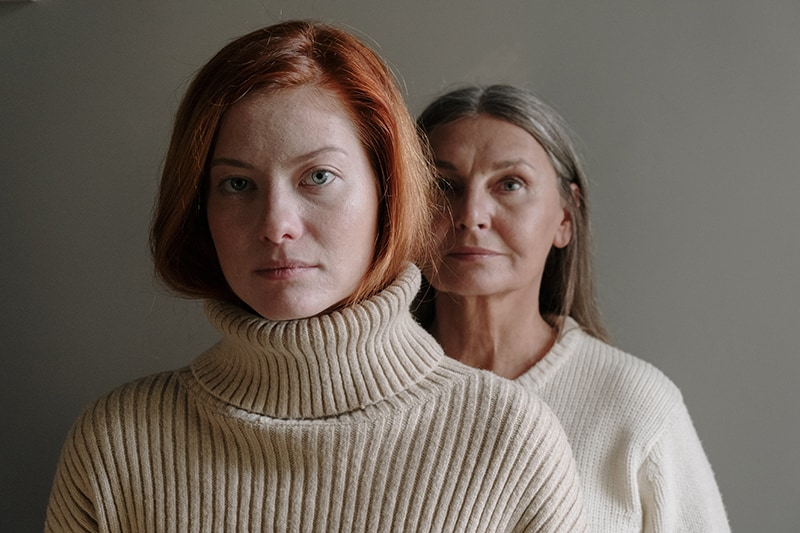 Frau mit roten Haaren, die vor einer älteren Frau mit grauen Haaren steht