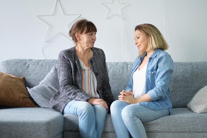 Frau sitzt mit Schwiegermutter während des Gesprächs auf der Couch