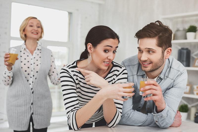 Freudlose junge Frau, die mit ihrem Mann spricht, während sie auf ihre Schwiegermutter zeigt