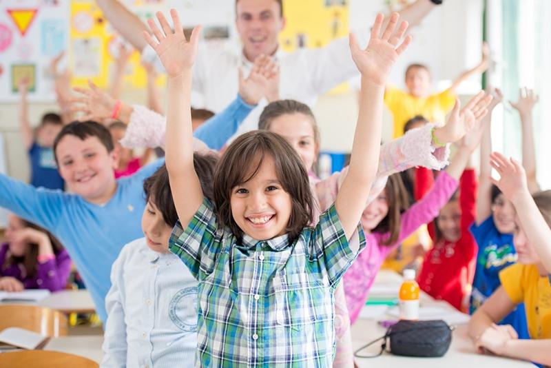 Fröhliche Gruppe von Kindern mit ihrem Lehrer im Klassenzimmer