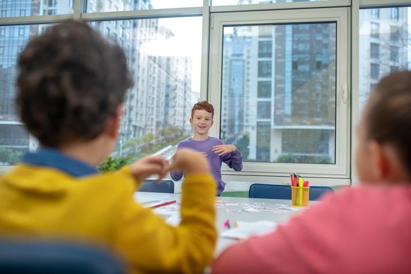 Fröhlicher Schüler steht vor dem Klassenzimmer und erklärt etwas mit den Händen