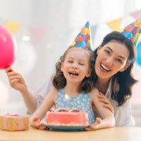 Tante und Tochter feiern Geburtstag mit Kuchen zu Hause