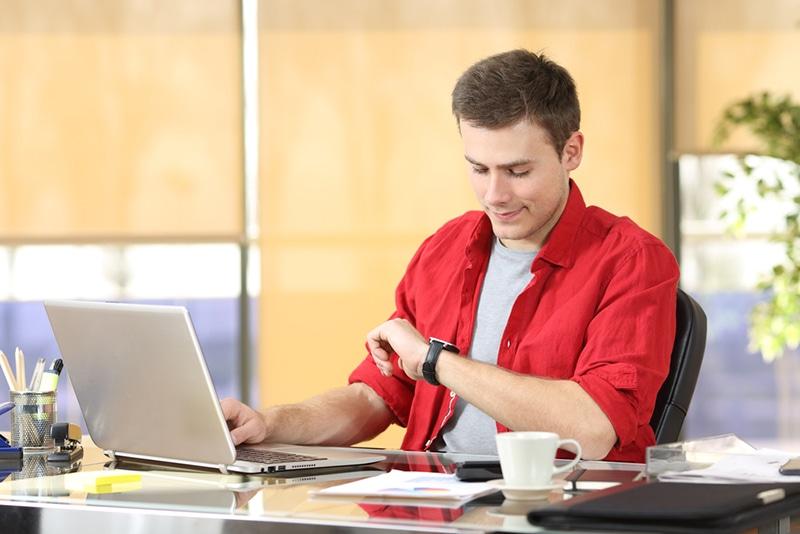 Geschäftsmann, der die Uhr beim Sitzen am Schreibtisch arbeitet und überprüft