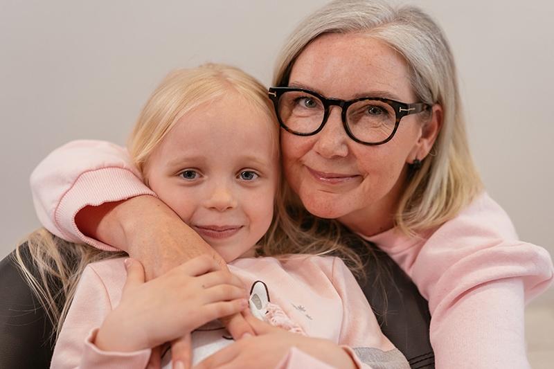 Großmutter, die ihre Enkelin von hinten umarmt